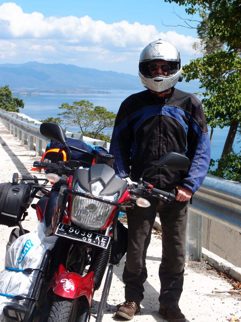 motorcycle and rider stopped alongside the highway in Sumbawa